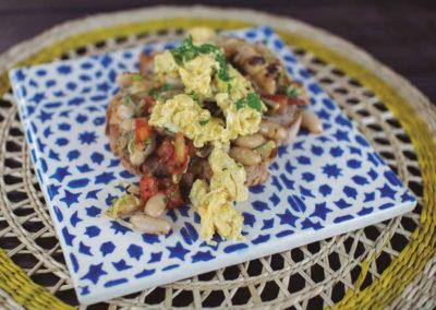 Ovos mexidos sobre tosta de pão de mistura e feijão com tomate